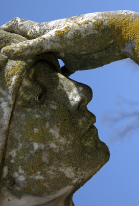 statue of a face with a hand on forehead